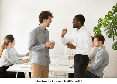 Friendly multiracial young colleagues chatting together in office during coffee break, diverse coworkers talking and laughing at funny joke having good relations and pleasant conversation at work