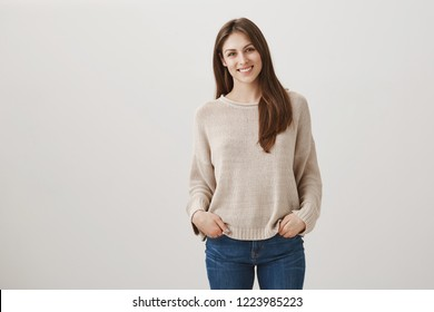 Friendly newbie meets with new teammates. Indoor shot of shy attractive female in casual pullover standing with hands in pockets and tilting head while smiling at camera, talking to stranger
