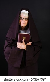 A friendly nun holding a bible