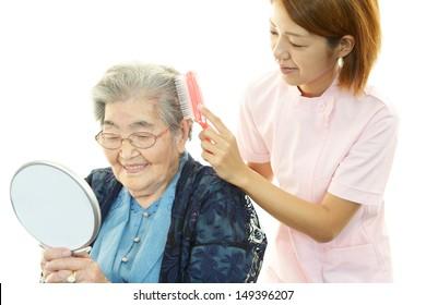 Freundliche Krankenschwester kümmert sich um eine ältere Frau