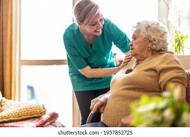 Freundliche Krankenschwester, die eine ältere Dame unterstützt