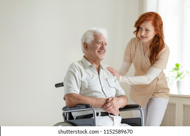 Friendly nurse supporting smiling paralyzed senior man in a wheelchair