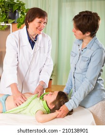 Friendly old female pediatrician doctor examining child at clinic