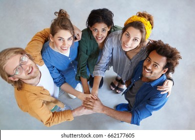 Friendly people of different races looking from above holding their hands together embracing each other rejoicing their victory. Diversity, teamwork, cooperation, ethnicity and people concept