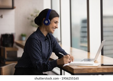 Friendly polite hindu female in earphones client support manager look at laptop screen listen take note of customer complaint. Indian woman student talk to teacher at remote lesson in conference mode