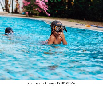 Friendly portrait of a two playful and cheerful kids they swimming in a pool and diving into the water in daytime.