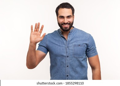 Friendly positive bearded man in blue shirt greeting you rising hand and waving, saying hi, glad to see you, looking at camera with toothy smile. Indoor studio shot isolated on white background