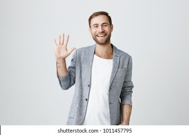 Friendly positive smiling bearded man in trendy jacket over white t-shirt and waving with his hand, hailing business partners at meeting. Good-looking businessman greets someone