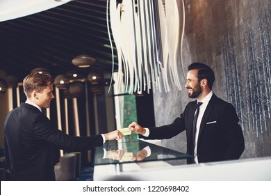 Friendly receptionist. Cheerful friendly young businessman smiling and giving his gold card to the professional receptionist