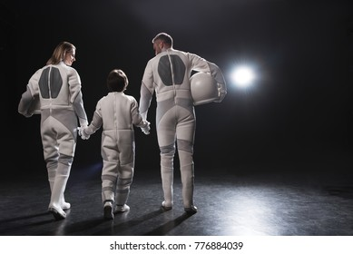 Friendly relations. Back view of positive family of astronauts are going together while holding by hands. Mother and father are looking at their little son. Dark background with copy space