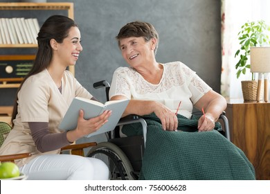 Friendly relationship between senior woman in wheelchair and caregiver reading book at loud