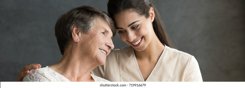 Friendly relationship between smiling caregiver in uniform and happy elderly woman