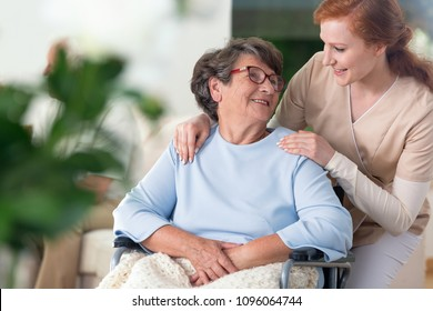 Friendly relationship between smiling nurse and happy disabled grandmother