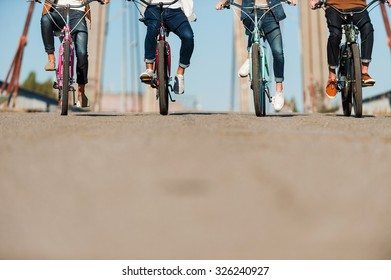 Friendly ride. Cropped image of four people riding bicycles along the bridge