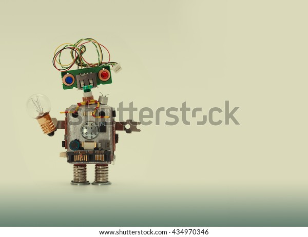 Friendly robot with light bulb. Funny robotic toy on beige gray gradient background. Blank space
