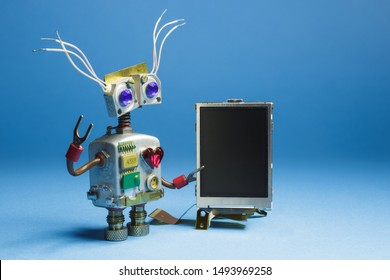 Friendly robot toy with digital empty black board in his hand. Funny mechanical toy character.