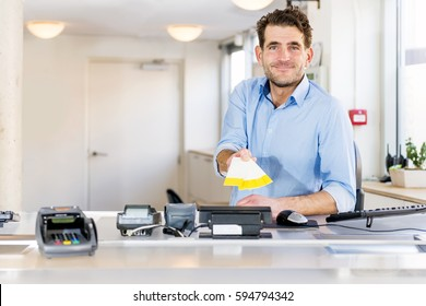 Friendly sales clerk handing over tickets for an event, sitting behind a counter at a ticket booth, smiling.