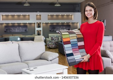 Friendly sales consultant demonstrating samples of upholstery fabric in furniture shop