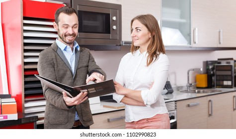Friendly salesman offering young female client material for kitchen furniture at a salon. Focus on both persons