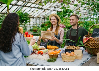 Friendly saleswoman in apron and hat is selling organic food vegetables during farm sale in greenhouse. Small business, working youth and shopping concept.