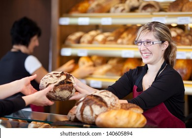 friendly saleswoman in bakery passing bread over the counter