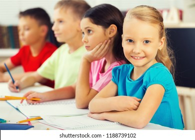 Friendly school children on blurred classroom background
