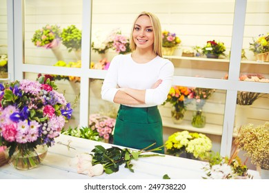 Friendly seller of fresh flowers looking at camera