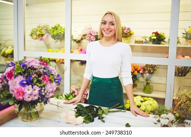 Friendly seller of fresh flowers standing by her workplace
