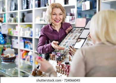 Friendly seller helps customers choose cosmetics in store