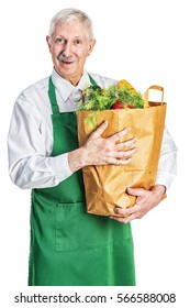 Friendly senior male grocer in a green apron, standing with a paper bag full of fresh groceries and a smile on his face
