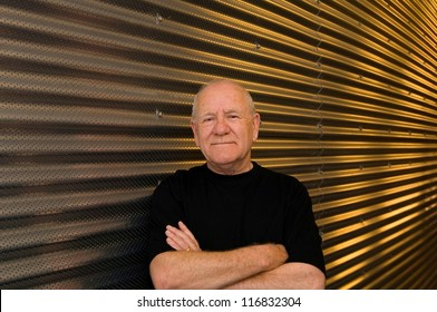 Friendly senior man standing in front of a wall
