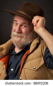 Friendly senior man tipping his hat