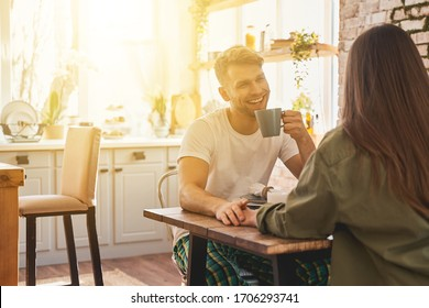 Friendly smile. Kind young man drinking tea while looking at his girlfriend, spending weekend at home