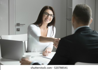 Friendly smiling businessman and businesswoman handshaking over the office desk after pleasant talk and effective negotiation, good relationships. Business concept photo