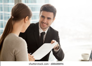 Friendly smiling businessman giving official document to businesswoman, offering paper for signing after successful negotiations under contract, initiating good business deal, collaboration proposal