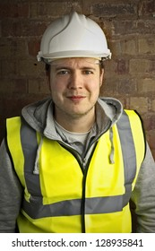friendly smiling construction worker / builder against brick wall background