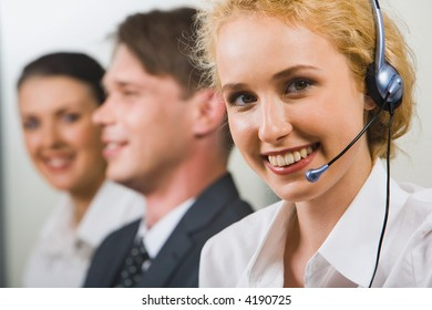 A friendly smiling customer support operator on a background of two business people
