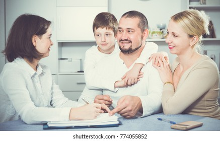 Friendly smiling family discussing house reconstruction project with female designer at home