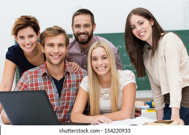 Friendly smiling group of young male and female college or university students grouped together around a laptop computer posing for the camera