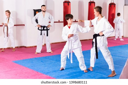 Friendly smiling  kids in kimonos exercising techniques in pair during taekwondo class at gym