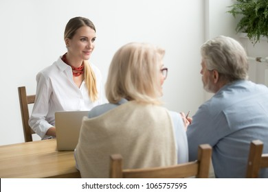 Friendly smiling lawyer consulting older clients, senior couple asking advice about making investment at meeting with female financial advisor or bank worker, consultation or job interview concept