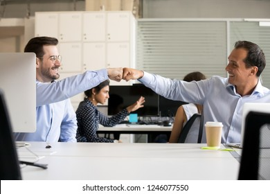 Friendly smiling male colleagues fist bumping at workplace, happy coworkers sharing success, middle-aged men celebrating good teamwork result, satisfied by collaboration, cooperation at work, respect