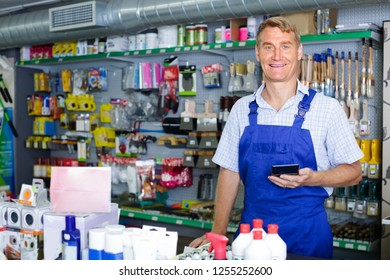 friendly smiling man seller wearing uniform standing at pay desk in housewares store