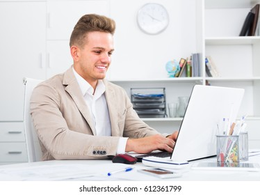 friendly smiling manager working efficiently at office desk with laptop