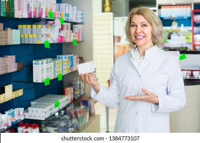 Friendly smiling mature female technician working in pharmacy