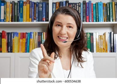 Friendly smiling mature teacher with headphones and white blazer in front of a bookshelf in an office, teaching via an online video call, telelearning
