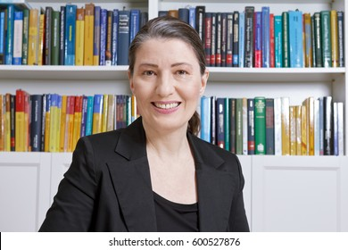 Friendly smiling mature woman with black blazer in an office with lots of books, professor, teacher, translator, lawyer, trustee, accountant or businesswoman