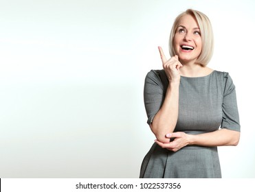 Friendly smiling middle-aged woman pointing at copyspace isolated on white background