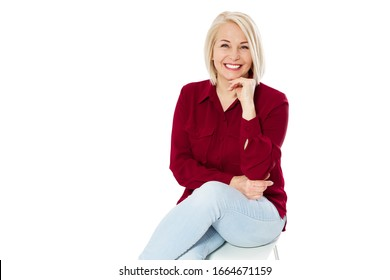 Freundlich lächelnde Frau mittleren Alters auf Stuhl einzeln auf weißem Hintergrund