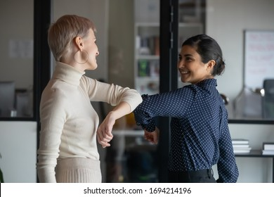 Friendly smiling millennial diverse female colleagues keeping social distance, greeting each other by bumping elbows instead of hugs or handshaking, preventing covid 19 coronavirus infection spread. - Shutterstock ID 1694214196